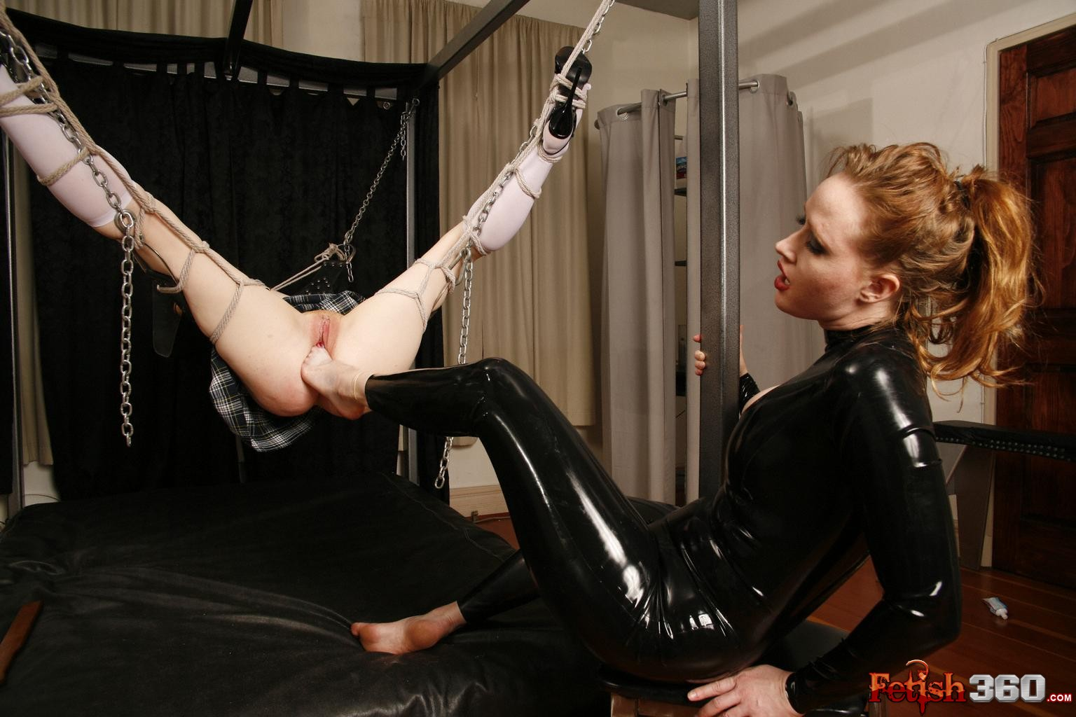 Julie Madison in latex rubber shoving her foot in a slave's pussy while slave is suspended in air